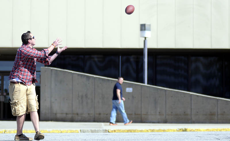 "Zach Montell collects a pass Monday while playing catch outside the Central Maine Commerce Center in Augusta. Montell, Jordan Cloutier, right, Aaron Howard and Chris Owen took a break from their sales jobs at Access Worldwide to chuck the pigskin the morning after the Patriots' first football victory of the season. ""They should have won by more than two points,"" Cloutier remarked."