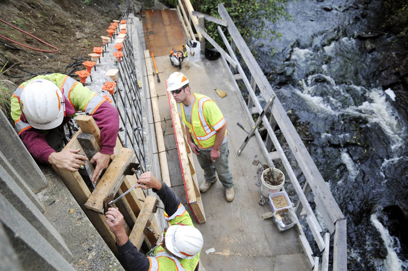 Maine Department of Transportation employees Lenny Sioch, left, Gary Ritter and Tim Clement secure wooden forms on a wing wall that retains Route 41 along the bridge spanning Mill Stream in Vienna on Tuesday. Workers from the state's bridge maintenance department will be spending three weeks adding metal rods to secure the walls and replacing the rails on the bridge in the center of the village.