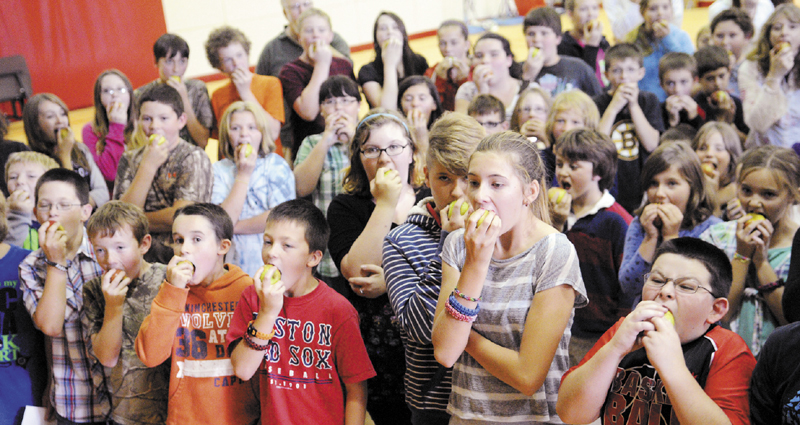 Whitefield Elementary School students take collective bites out of apples Thursday during a celebration of the locally grown fruit. Residents provided hundreds of apples to sample, all grown at local orchards, during the event, sponsored by the Focus on Agriculture in Rural Maine Schools.