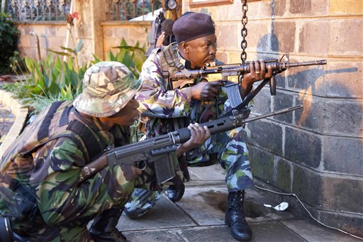 """Kenya security personnel take cover outside the Westgate Mall after shooting started inside the mall early Monday morning. Kenya's military launched a major operation at the upscale Nairobi mall and said it had rescued """"most"""" of the hostages being held captive by al-Qaida-linked militants during the standoff that killed at least 68 people and injured 175."""
