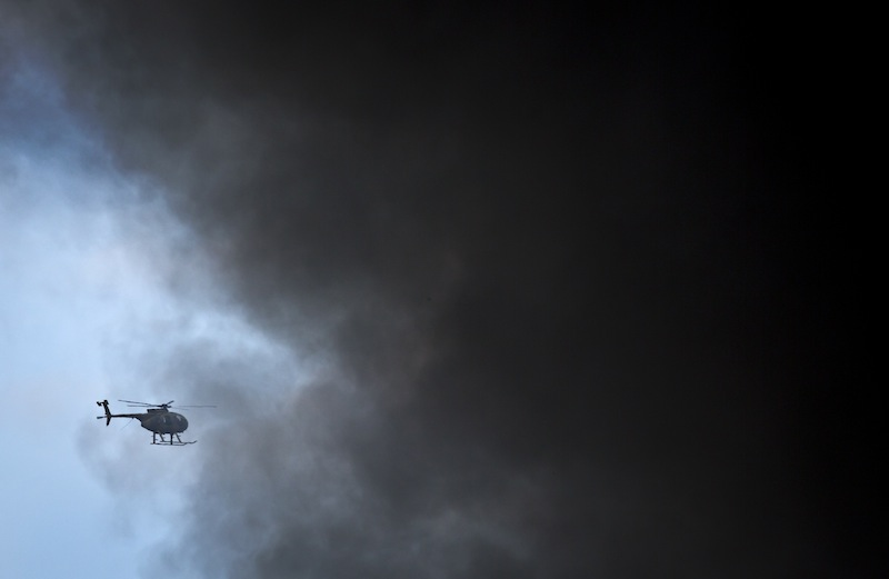 A Kenya Army helicopter flies behind a plume of black smoke billowing from the Westgate Mall, following large explosions and heavy gunfire, in Nairobi, Kenya Monday, Sept. 23, 2013. Four large blasts rocked Kenya's Westgate Mall on Monday, sending large plumes of smoke over an upscale suburb as Kenyan military forces sought to rescue an unknown number of hostages held by al-Qaida-linked militants. (AP Photo/Ben Curtis)