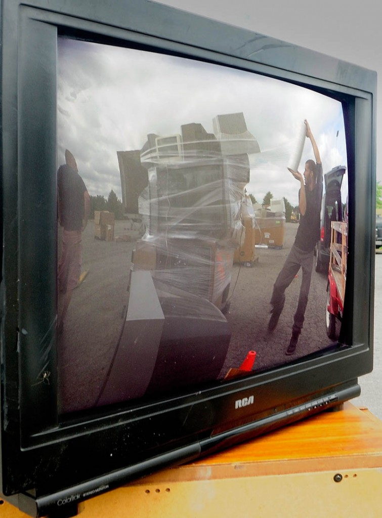 Matt McLeod, of eWaste Recycling Solutions, is reflected in the screen of an old television while wrapping up a stack of them on Saturday in the parking lot at the Augusta Civic Center. The event was a fundraiser for the United Way of Kennebec Valley's winter warming center, which opens in late December, according to executive director Rob Gordon, on Front Street near the gazebo, the same location it had last year.