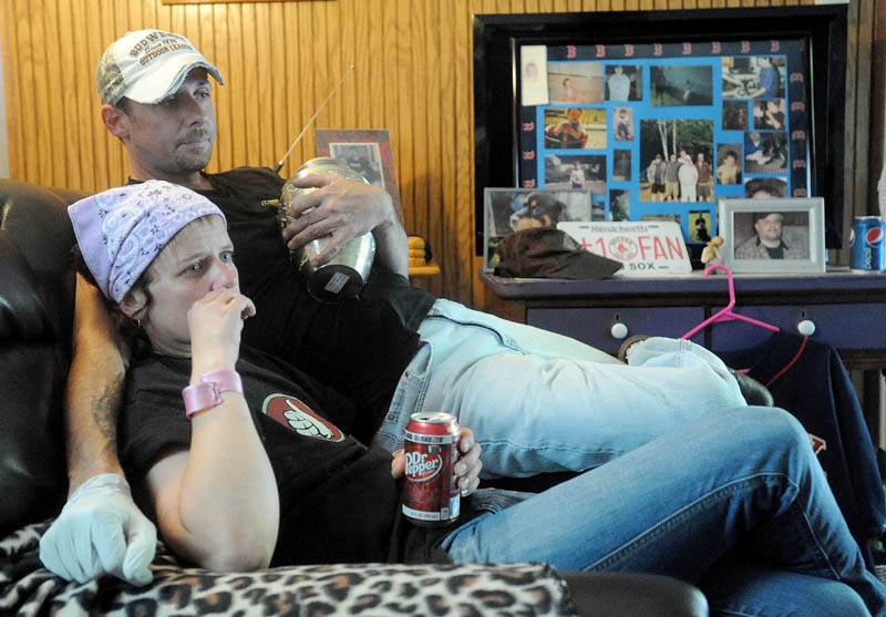 Melissa Nelson, 38, and Jeremy Nelson, 39, recall their brother Christopher Nelson's life, as Jeremy clutches his brother's remains, at the family's Pease Hill Road residence in Anson on Wednesday.
