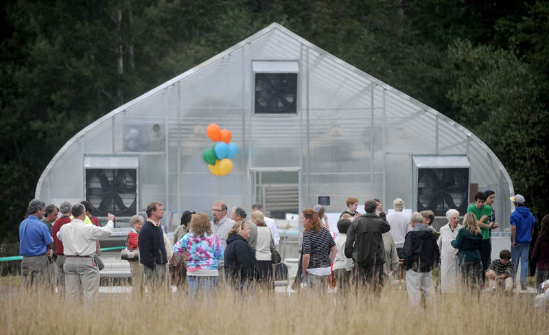 People gather around one of three newly erected greenhouses during their dedication at the Maine School of Natural Sciences in Hinckley today.