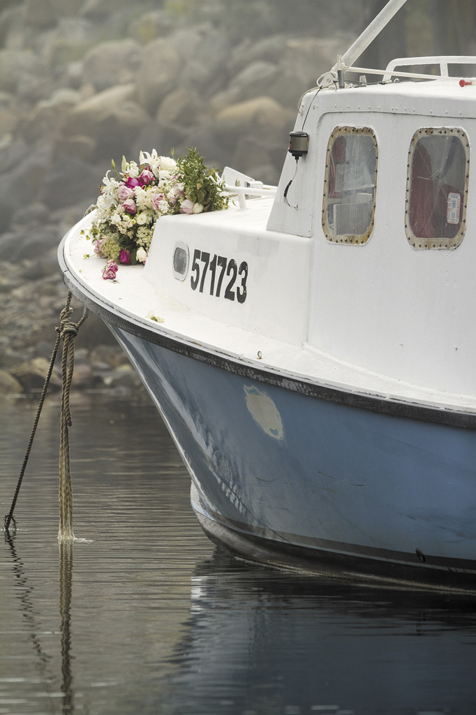 """Bouquets of flowers are set on the bow of the lobster boat """"Clover"""" in memorial of Billy McIntire in Perkins Cove on Wednesday, Aug. 28."""