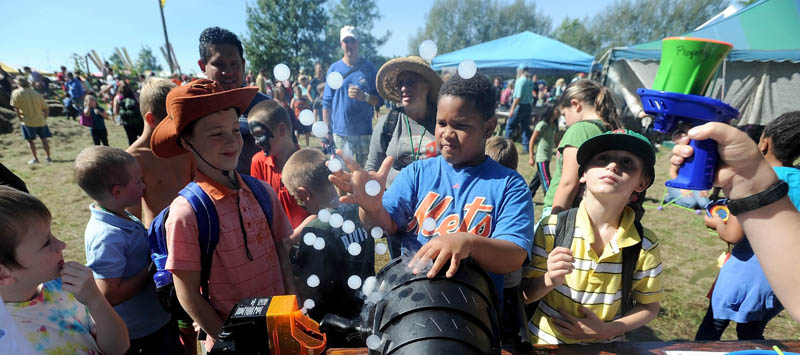 Angel Ortiz, 9, of Topsham, reaches for dry ice-filled bubble at the Mad For Science booth at the Common Ground County Fair in Unity today.