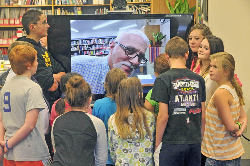 Victor Esposito, the master specialist for the Jobs for Maine's Graduates program at Vassalboro Community School, interacts with his combined 6th and 7th grade class in the school's library on Thursday. Esposito spent the first week of the school year teaching via an iPad, while in the hospital with cellulitis in his left foot.