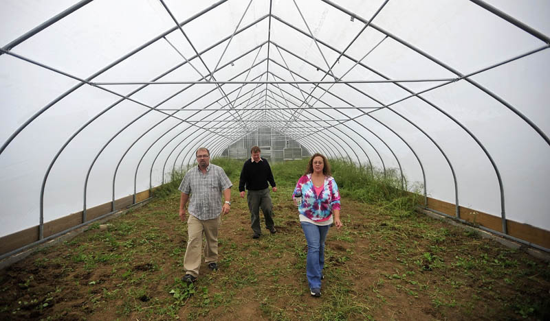 Jeff Chase, center, the agricultural specialist for the Maine School of Natural Sciences, offers a tour today to Mark Tulley, left, and Renee Gray, right, of one of three greenhouses recently erected at the Maine School of Natural Sciences in Hinckley.