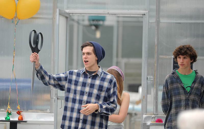Tim Thompson, 17, a senior at the Maine School of Natural Sciences, holds up the novelty scissors as Jeff Chase, the agriculture specialist for the school, is introduced, during the dedication today of three greenhouses at the Maine School of Natural Sciences in Hinckley.
