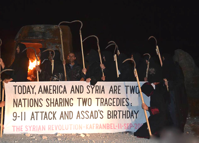 Citizen journalism image provided by Edlib News Network, which has been authenticated based on its contents and other AP reporting, show anti-Syrian regime protesters carrying a banner during a sit-in, at Kafr Nabil town, in Idlib province, northern Syria, on Wednesday.