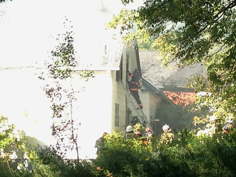 Firefighters climb ladders into a Pittston home Friday afternoon after a fire was reported.