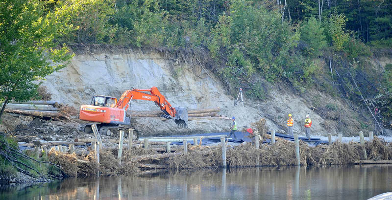 Constructions crews work on the eroded banks of the Sandy River near Whittier Road in Farmington today.