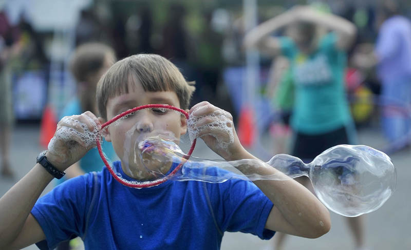 Charlie Frost, 9, of Canaan, blows bubbles through a form made from a giant pipe cleaner at Inland Hospital's Family Fun Day in Waterville today.