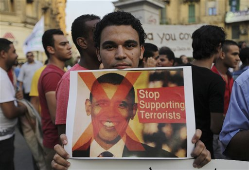 A demonstrator holds a placard with a picture of U.S. President Barack Obama during a protest against a possible strike against Syria, in Cairo, Egypt, on Sunday. Obama's decision to overrule his new foreign policy team's first decision to use of military force wound up being a stark lesson in the president's ability to overrule them all.