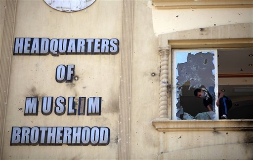 In this July 1, 2013, photo, an Egyptian protester ransacks the Muslim Brotherhood headquarters in the Muqatam district in Cairo.
