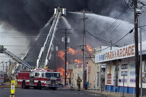 Firefighters battle a fire on the Seaside Heights, N.J. boardwalk on Thursday. The fire started in the vicinity of an ice cream shop and burned several blocks of boardwalk and businesses in a town that was still rebuilding from damage caused by Superstorm Sandy.