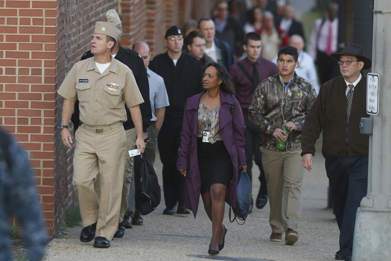 Military personnel and workers look towards an entrance of the Washington Navy Yard on Thursday, when the yard reopened after Monday's mass shooting.