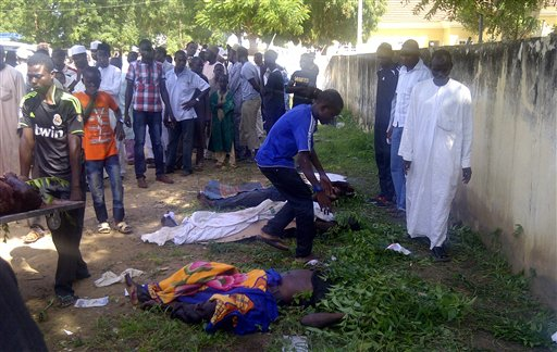 In this image taken with a mobile phone, rescue workers and family members gather to identify the shrouded bodies of students killed following an attack by suspected Islamist extremists on an agricultural college in Gujba, Nigeria, on Sunday.