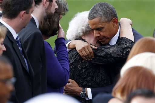 President Obama comforts a woman sitting in the family section at a memorial service Sunday for the victims of the Washington Navy Yard shooting.