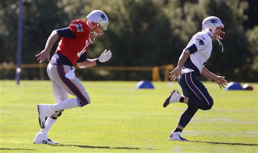 New England Patriots quarterback Tom Brady, left, and wide receiver Julian Edelman run across the field during a stretching and drills session before practice at the team's training facility in Foxborough, Mass., Wednesday.