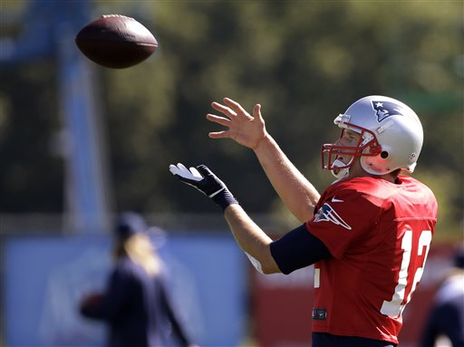 New England Patriots quarterback Tom Brady (12) catches a ball during a stretching and drills session before NFL football practice at the team's training facility in Foxborough, Mass., Wednesday.