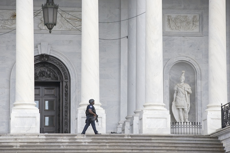 U.S. Capitol Police personnel keep watch on the East Plaza of the Capitol as the investigation continues at the nearby high-security Washington Navy Yard where gunmen went on a shooting rampage, Monday, Sept. 16, 2013, in Washington. (AP Photo/J. Scott Applewhite)