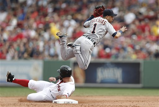 Detroit Tigers shortstop Jose Iglesias turns a double play over the slide of Boston Red Sox first baseman Mike Napoli during the second inning Monday at Fenway Park in Boston. The Tigers won 3-0.