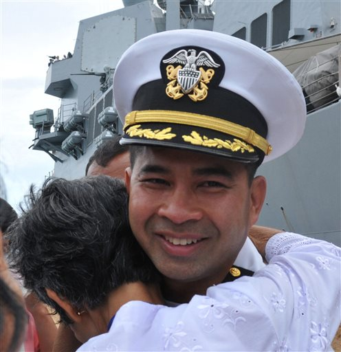 In this image provided by the U.S. Navy, Cmdr. Michael V. Misiewicz, then commanding officer of the guided-missile destroyer USS Mustin, is greeted by a member of his family as the Mustin arrives in Sihanoukville, Cambodia on Dec. 3, 2010.