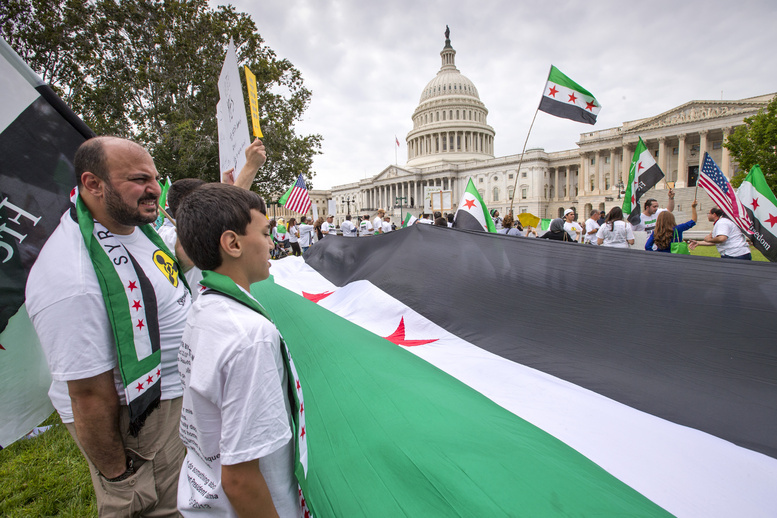 Waving the flag of the Syrian rebels, demonstrators opposed to the government of Syrian President Bashar Assad gather on the lawn of the U.S. Capitol in Washington on Monday.