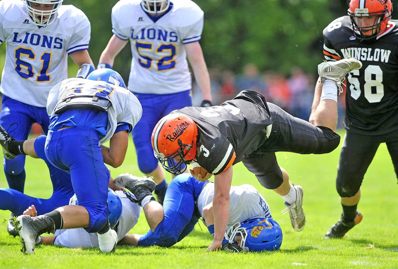 Staff photo by Michael G. Seamans Winslow High School running back Dylan Hapworth, 3, dives over a Belfast High School defender in the first quarter in Winslow on Saturday.