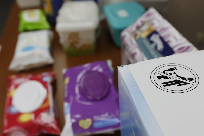In this photograph taken, Friday, Sept. 20, 2013, in Middlesex, N.J., the label that indicates wipes should not be flushed in a toilet is seen on a box next to baby wipes at the office of Rob Villee, executive director of the Plainfield Area Regional Sewer Authority in New Jersey. Increasingly popular bathroom wipes, thick, premoistened towelettes that are advertised as flushable, are creating clogs and backups in sewer systems around the nation. The problem has gotten so bad in this upstate New York town that frustrated sewer officials traced the wipes back to specific neighborhoods, and even knocked on doors to break the embarrassing news to residents that they are the source of a costly, unmentionable mess. An industry trade group this month revised its guidelines on which wipes can be flushed, and has come out with a universal stick-figure, do-not-flush symbol to put on packaging. (AP Photo/Julio Cortez)
