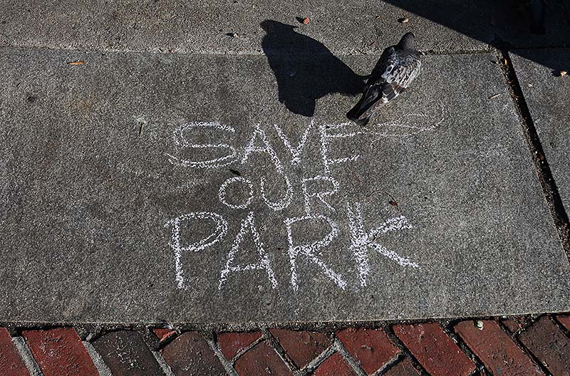 A pigeon walks past a message written in chalk protesting the sale of part of Congress Square Plaza.