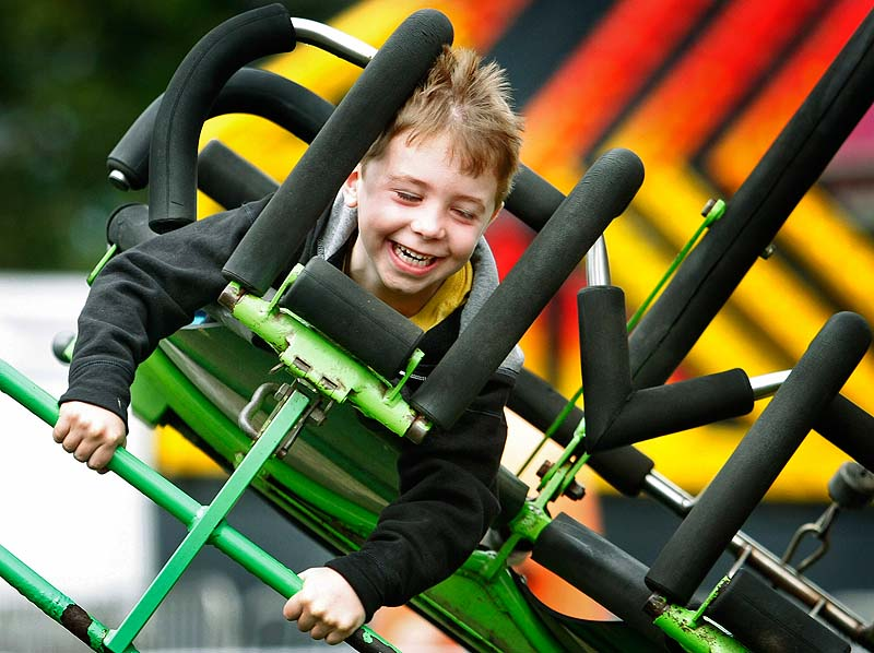 Ben Duda, 6, of Boston, Mass., flies for the first time on the Cliff Hanger ride with his grandfather, Fred Miller, of Freeport at opening day of the Cumberland County Fair on Sunday.
