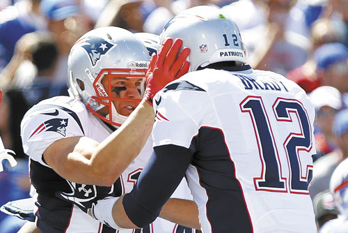 NICE PASS: New England's Julian Edelman, left, celebrates with teammate Tom Brady, right, after catching a touchdown pass during the first half against Buffalo on Sunday in Orchard Park, N.Y.