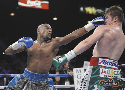TAKE THAT: Floyd Mayweather Jr. lands a punch to the face of Canelo Alvarez in the third round during a 152-pound title fight Saturday in Las Vegas. Mayweather won with a unanimous decision.