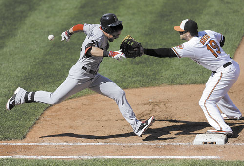 PAINFUL OUT: Boston's Jacoby Ellsbury, left, runs toward first base as Baltimore first baseman Chris Davis reaches for a throw in the fourth inning Sunday in Baltimore. Ellsbury advanced to second base on a throwing error by catcher Steve Clevenger, Jarrod Saltalamacchia scored on the play and Davis left the game with an injury.