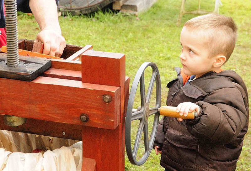 Rannon Rines, 3, of Greene, turns the handle on a cider press during AppleFest events last year at The Monmouth Museum. The events included fresh apples and apple pie for sale and a 5K road race earlier in the morning.