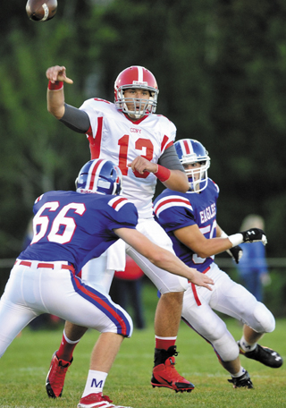 BIG PLAY: Cony High School quarterback Ben Lucas, 13, center, unloads the ball before getting hit my Messalonskee High School defenders Caleb Bean left, and Jordan Carson, in the first quarter on Friday at Messalonskee High School in Oakland.