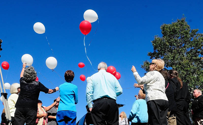 People watch a balloon release following the groundbreaking ceremony for the Maine chapter of Parents of Murdered Children's new monument today in Holy Family Cemetery in Augusta.