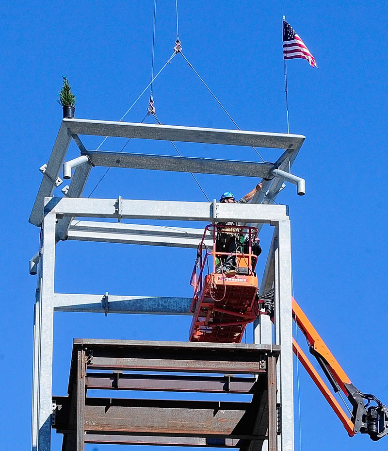 Construction workers guide the last beam into place on Wednesday at the new consolidated courts building being built in Augusta.