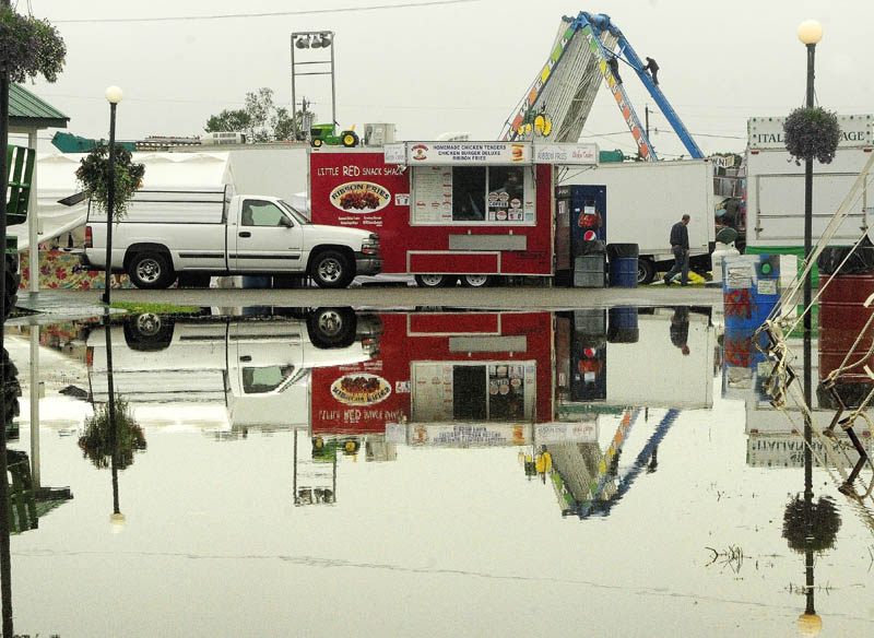Workers climbing down from dismantling the Ferris wheel are reflected in a large puddle today at the Windsor Fair. Except for the 4-H livestock auction, all fair events were cancelled today because of the heavy rain in the morning.