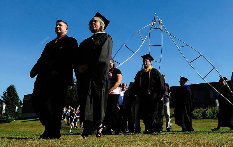Rising Scholars and the professor that nominated them walk under a sculpture during the convocation at the University of Maine at Augusta today.
