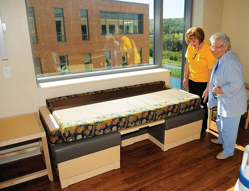 Nurse manager Edie Welch shows her mother, Lillian Merrill, how a couch in a patient room folds into a bed during a tour of the Alfond Center for Health today in Augusta. Welch was giving tours of the David M. Dick Memorial Wing, which is named in honor of a late nurse who worked for the hospital for 20 years.