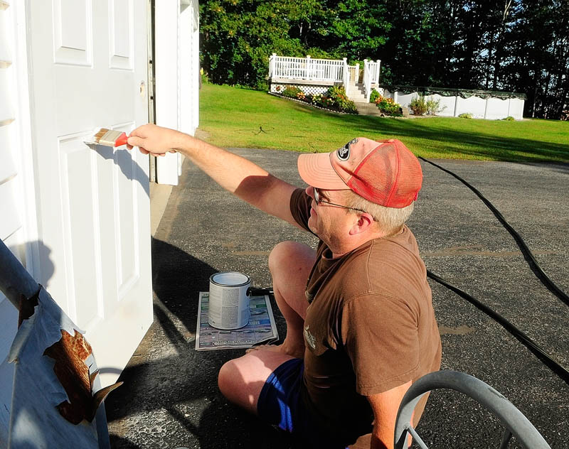 David Willman paints a door on Friday at his Augusta home on Old Belgrade Road, near the new MaineGeneral regional hospital. Willman said that it was just regular maintenance that he'd be doing anyway regardless of whether or not the house is for sale.