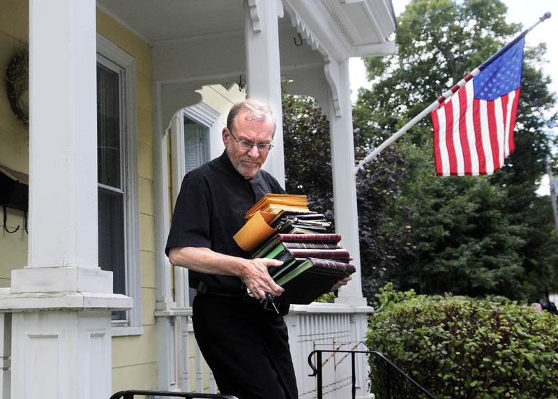 The Rev. Frank Morin carries the sacramental registers from the rectory of Sacred Heart Catholic Church in Hallowell on Thursday. The priest at Sacred Heart, George Hickey, recently passed away, leaving the church without a pastor. The paper records of baptisms, first communions, confirmations, marriages and deaths were relocated to St. Michael Catholic Parish to be stored with other church documents, according to Morin, the parish administrator.