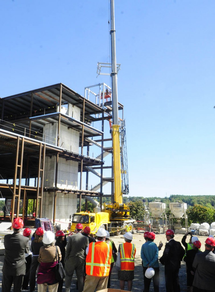 People watch as the last beam is swung into place.