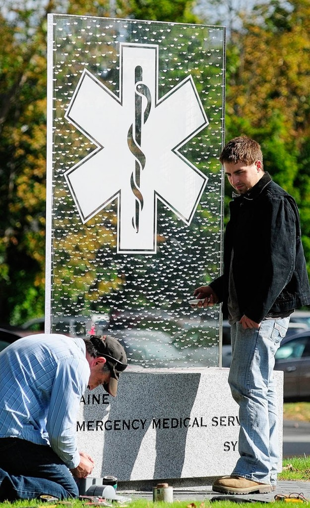 Robert Antognoni, left, hooks up wires for LED lights as Robert E. Antognoni waits with a remote control to test them on Thursday at the Maine Emergency Medical Services monument being built in in Augusta. The father and son electricians, from Randolph, were wiring up the lights that will shine from under the clear monument on State Street, between the police and fire memorials on the State House complex grounds.