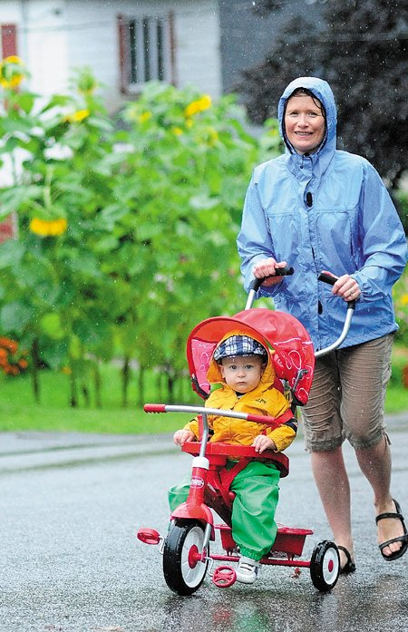 Oliver Gadebirk-St. Pierre, 14 months, gets pushed by his mother, Sine Gadebirk-St. Pierre, in the rain today in Hallowell. She said the rainy holiday weather wasn't going to interfere with a walk through their neighborhood. The National Weather Service reported that over two inches of rain fell at the Augusta State Airport through 2 p.m. today.