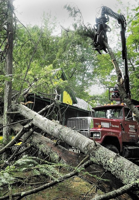 A crew from Hickey Logging cleans up several fallen trees on Thursday at a camp on the banks of Cobbossee Lake in West Gardiner. Several trees on the property were blown during a thunderstorm on Wednesday night. Owners Jack Boynton and Gail Andrews said that they'd been standing on the porch watching lightning over water when the trees fell right in front, but not on top, of the camp.
