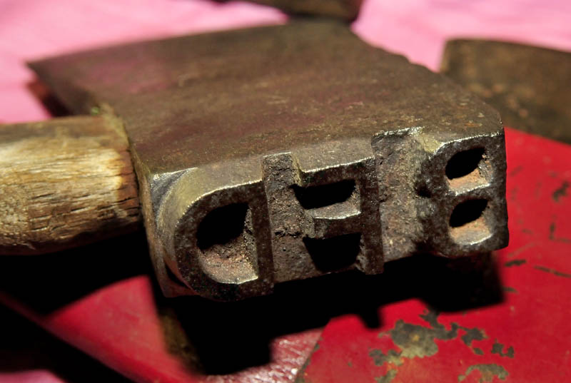 """An ax head in Howard Hardy's collection bears the initials """"BFD,"""" for the logging company Bert, Forester and Dixfield. The tool was used to mark log ends during river drives, Hardy said."""